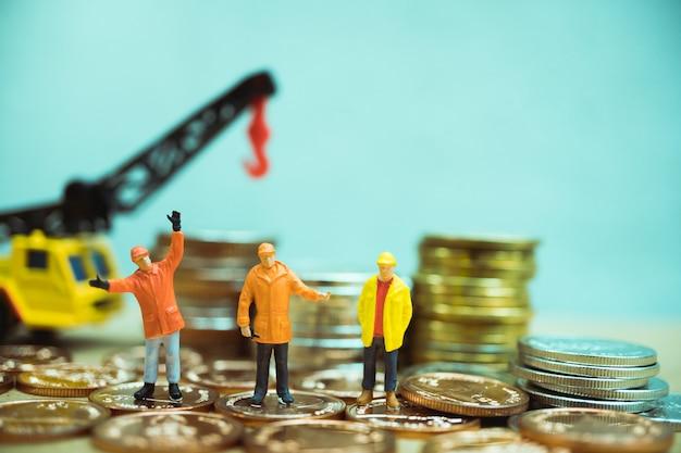 Pessoas em miniatura, equipe de engenheiro em pé na pilha de moedas com veículo guindaste