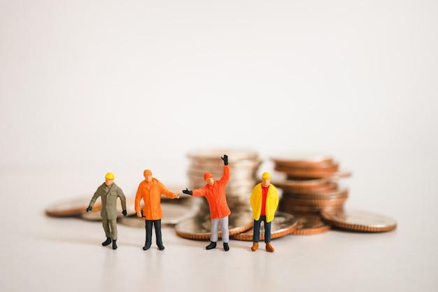 Pessoas em miniatura, equipe de engenheiro em pé na pilha de moedas usando como finanças e negócios