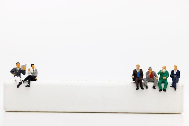 Pessoas em miniatura: equipe de negócios lendo livro na caixa de madeira branca.
