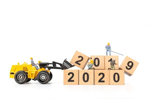 Pessoas em miniatura: equipe de trabalhadores cria número de blocos de madeira 2020