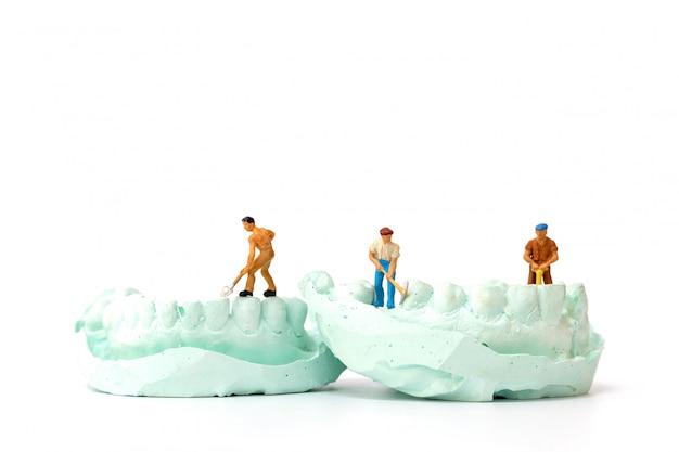 Pessoas em miniatura: equipe de trabalhadores reparando um dente