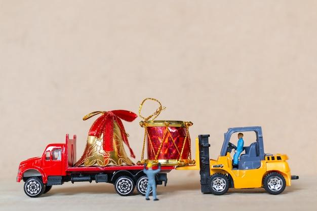 Pessoas em miniatura, equipe de trabalhadores trabalhando com uma decoração de natal