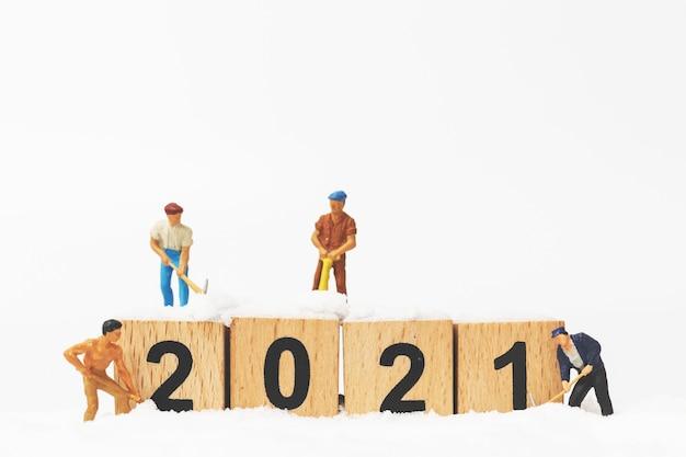 Pessoas em miniatura: equipe de trabalho cria o bloco de madeira número 2021, conceito de feliz ano novo