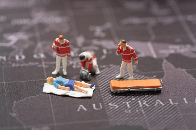 Pessoas em miniatura, equipe médica de emergência no trabalho na cena do acidente no mapa do mundo.