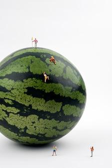Pessoas em miniatura escalando melancia