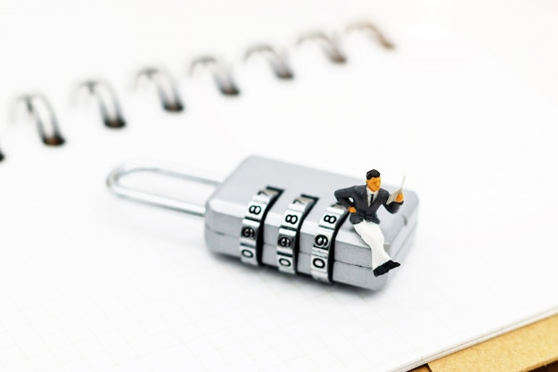 Pessoas em miniatura estão descriptografando o cadeado de desbloqueio, descriptografam a chave.