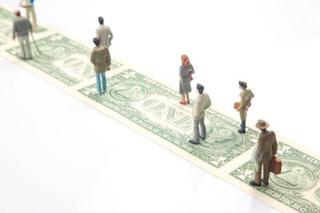 Pessoas em miniatura. estatuetas de pessoas percorrem o caminho do dinheiro em dólares para o sucesso na vida. conceito de independência financeira