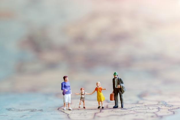 Pessoas em miniatura: família caminhando de mãos dadas com no mapa vintage.