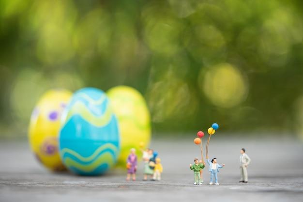 Pessoas em miniatura, família comemorando o dia de páscoa com ovos de páscoa coloridos
