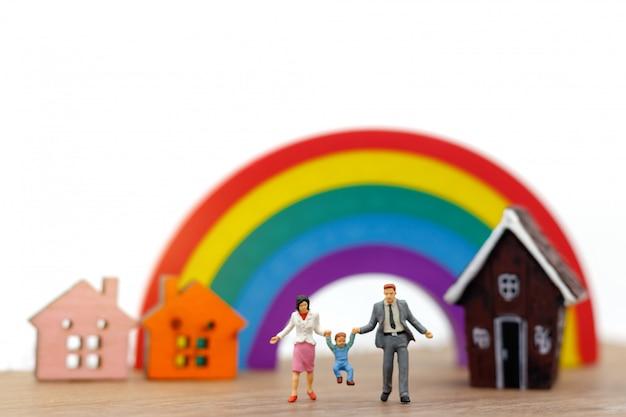 Pessoas em miniatura: família e crianças desfrutam com casa e arco-íris.