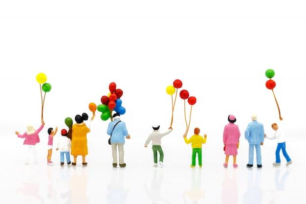 Pessoas em miniatura: família e filhos desfrutam com balões coloridos, conceito feliz dia da família.