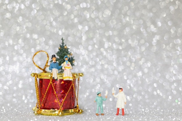 Pessoas em miniatura, família feliz comemorando um conceito de natal, natal e feliz ano novo.