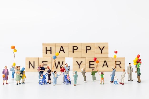 Pessoas em miniatura: família feliz, de pé no bloco de madeira feliz ano novo