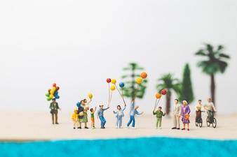 Pessoas em miniatura: família feliz desfrutar de férias de verão na praia