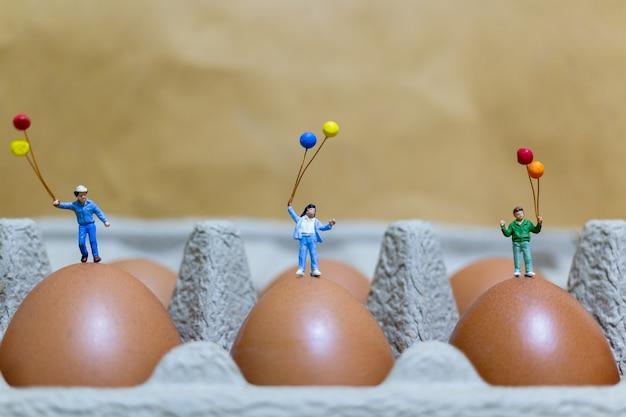 Pessoas em miniatura: família feliz segurando balão comemorando ovos de páscoa