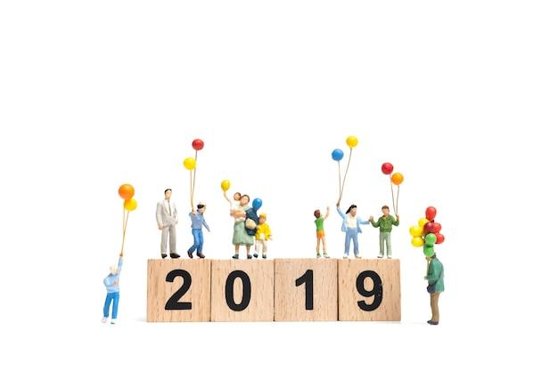 Pessoas em miniatura: família feliz segurando balão no número 2019 e cópia espaço para texto