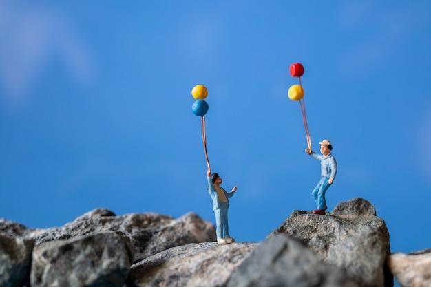 Pessoas em miniatura, família feliz, segurando o balão na rocha com céu azul