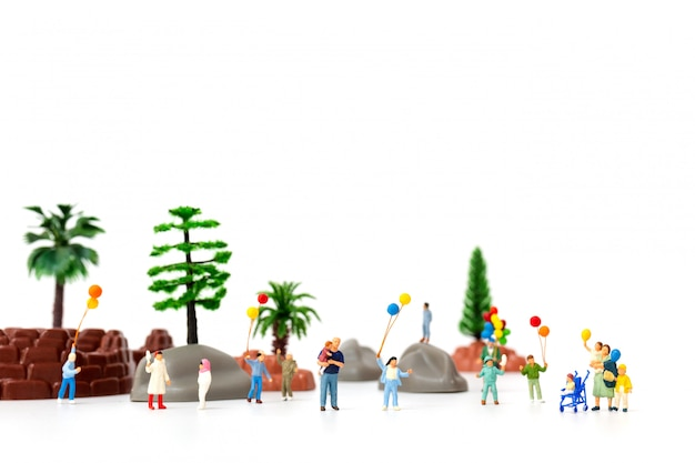 Pessoas em miniatura: família feliz, segurando o balão no parque