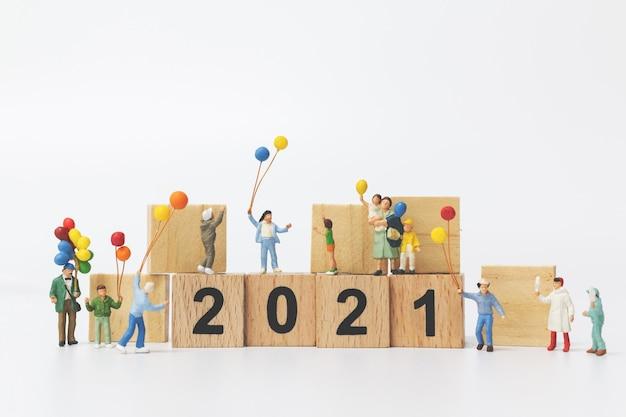 Pessoas em miniatura família feliz segurando um balão no bloco de madeira número 2021, conceito de feliz ano novo