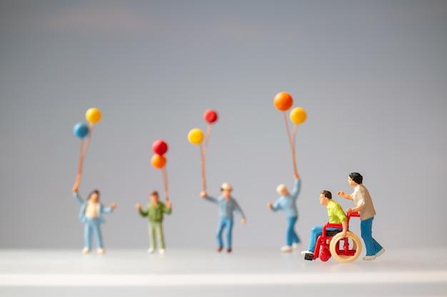 Pessoas em miniatura família positiva cuidando de seu pai deficiente