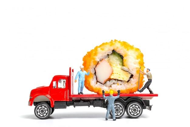 Pessoas em miniatura fazem sushi rolls no caminhão, conceito de entrega de comida