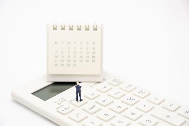 Pessoas em miniatura fila de pagamento renda anual (imposto) do ano na calculadora.