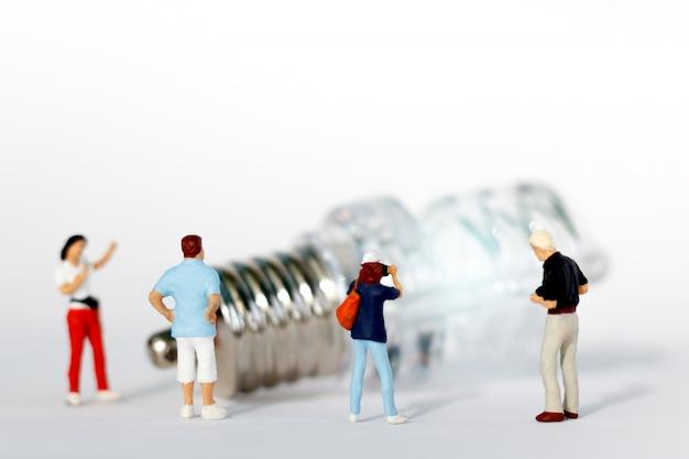 Pessoas em miniatura: fotógrafo tira uma foto da lâmpada. conceito de negócio de idéia