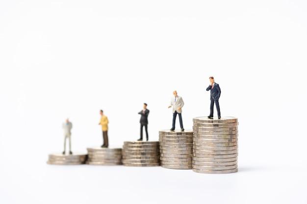 Pessoas em miniatura, homem de negócios permanente na pilha de moedas.