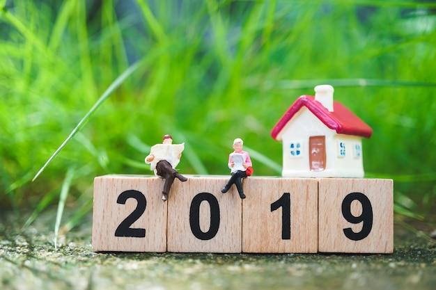 Pessoas em miniatura, homem e worman lendo no ano de bloco de madeira 2019 com mini casa