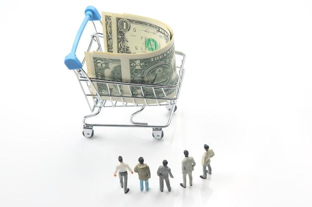 Pessoas em miniatura. homens de negócios ficam perto do dinheiro do dólar em uma cesta de supermercado. conceito de empreendedor de negócios