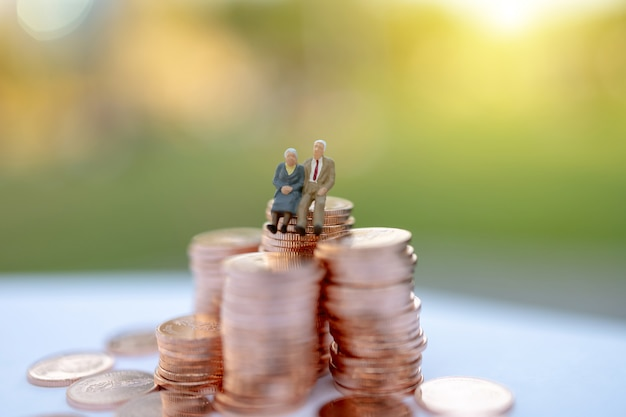 Pessoas em miniatura: idosos felizes sentados na pilha de moedas, aposentadoria e seguro de vida conceito.