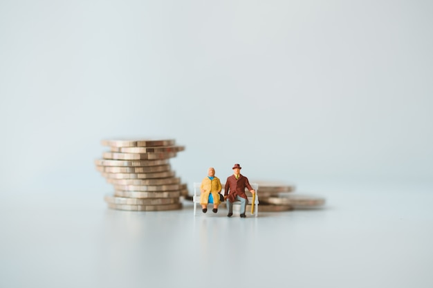 Pessoas em miniatura, idosos sentados em moedas de pilha usando como conceito de aposentadoria de emprego