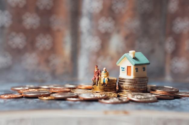 Pessoas em miniatura, idosos sentados em moedas de pilha