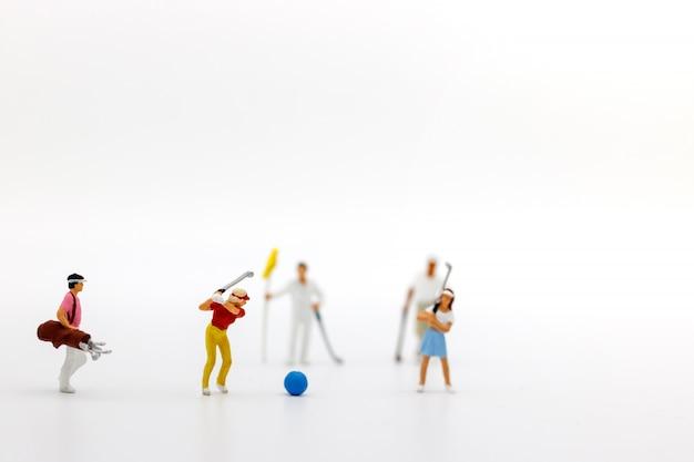 Pessoas em miniatura: jogadores de golfe batem bolas de golfe para a frente. alvo e crescimento no conceito de negócio.