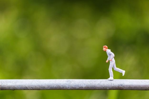 Pessoas em miniatura: jovens correndo em um fio