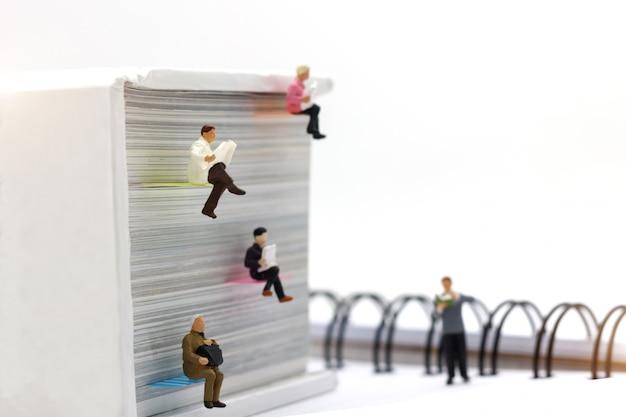 Pessoas em miniatura lendo com livro, educação ou conceito de negócio.