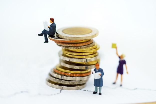 Pessoas em miniatura: livro de leitura da equipe de negócios na pilha de moedas.