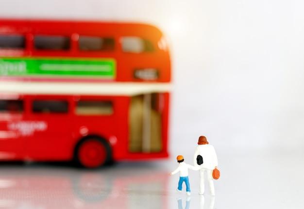 Pessoas em miniatura, mãe com filhos caminhando para o ônibus escolar.