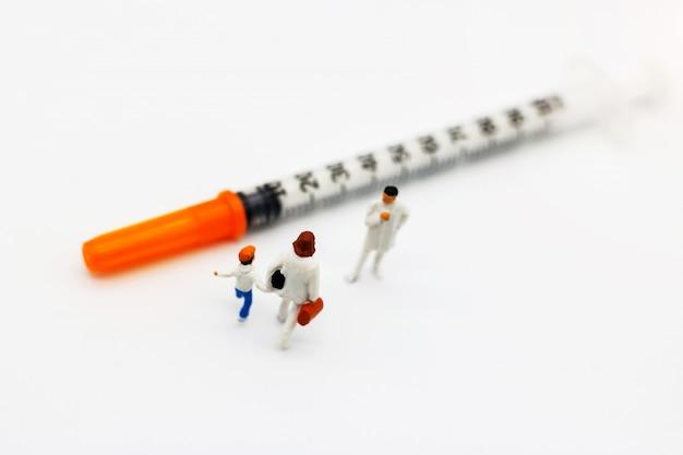 Pessoas em miniatura, mãe e filhos encontram médico com seringa