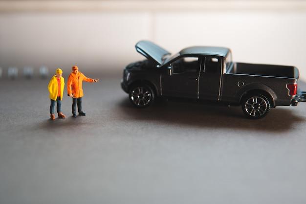 Pessoas em miniatura, mecânico de automóveis em pé com caminhonete avaria usando como conceito automotivo