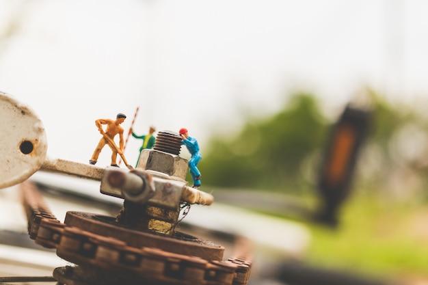 Pessoas em miniatura: mecânicos consertando bicicleta