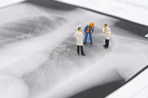 Pessoas em miniatura médico e trabalhador da construção civil no raio-x do pulmão para verificar se há vírus covid 19 ou coronavírus