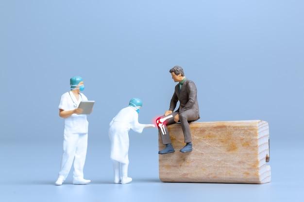Pessoas em miniatura médicos tratam reumatismo, osteoartrite, conceito do dia mundial da artrite