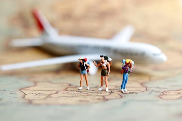 Pessoas em miniatura, mochileiros com avião.