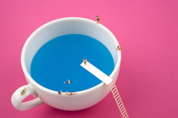 Pessoas em miniatura na caneca copo piscina