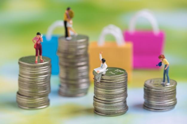Pessoas em miniatura na pilha de moedas
