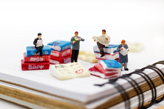 Pessoas em miniatura: negócio equipe lendo livro, educação ou conceito de negócio.