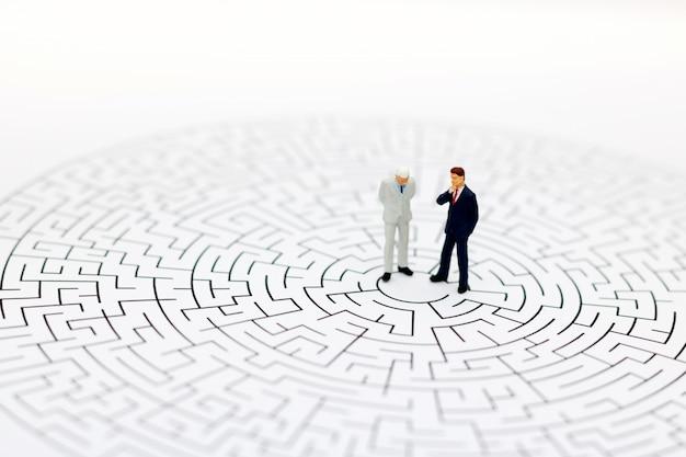 Pessoas em miniatura no centro de um labirinto