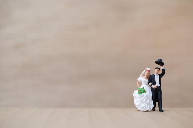 Pessoas em miniatura: noiva e noivo em fundo de madeira
