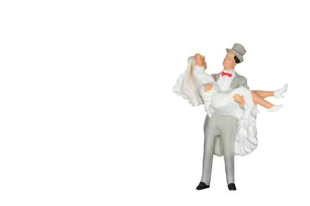 Pessoas em miniatura: noiva e noivo isolado no branco